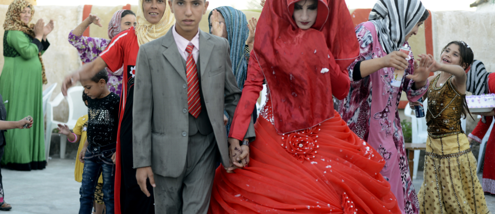 Hussein Younis Ali, 14 walks with his bride Nada Ali Hussein, 17, during the wedding party at his home in Tikrit, 150 km (93 miles) north of Baghdad, October 8, 2013. Boys and girls are married at an early age in Iraq's rural areas by local clerics who ignore Iraq's law that forbids under-aged marriages under the age of 16. Picture taken October 8, 2013. REUTERS/Bakr al-Azzawi  (IRAQ - Tags: SOCIETY) - RTX149QY