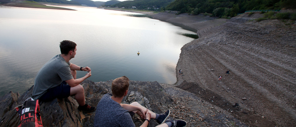 Young men relax at the bank of the Edersee reservoir with low water level near Waldeck, Germany July 21, 2017. Picture taken July 21, 2017. REUTERS/Ralph Orlowski - RC17FA9443E0