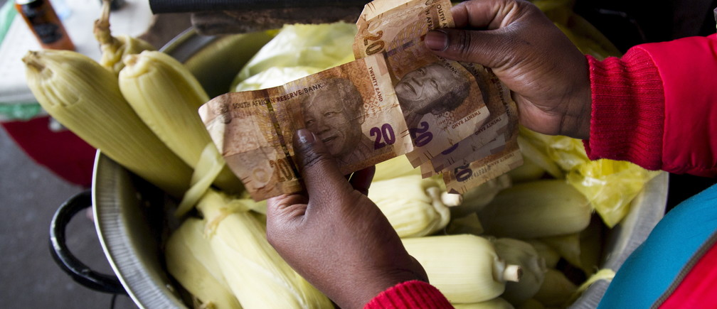 A street trader counts out change for a customer in Durban, September 8, 2015. South Africa's rand firmed more than 1 percent against the dollar, recovering from record lows in the previous session as bets on a rate hike in United States faded due to worries over global growth. The rand rose 1.04 percent to 13.8150 per dollar. REUTERS/Rogan Ward - RTX1RMVH