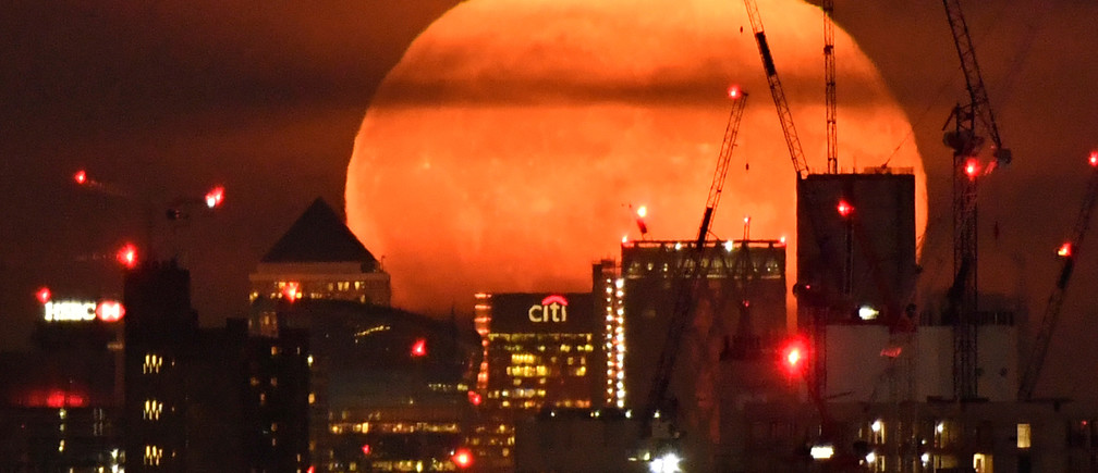 The full moon is seen rising behind skyscrapers at Canary Wharf and the London skyline, London, Britain, September 14, 2019. Picture taken on September 14, 2019. REUTERS/Toby Melville - RC150895F360