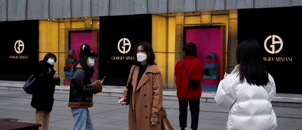People wearing face masks are seen outside a Giorgio Armani store at a shopping mall in Wuhan, Hubei province, the epicentre of China's coronavirus disease (COVID-19) outbreak, March 30, 2020. REUTERS/Aly Song