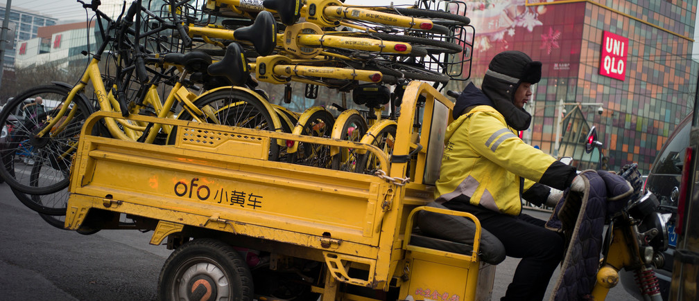 A worker transports bicycles for bike-sharing startup Ofo in Beijing, China.