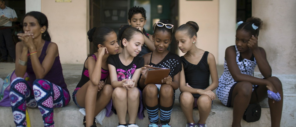 Children play with a tablet before performing at the first day of a contemporary urban dance festival in downtown Havana,