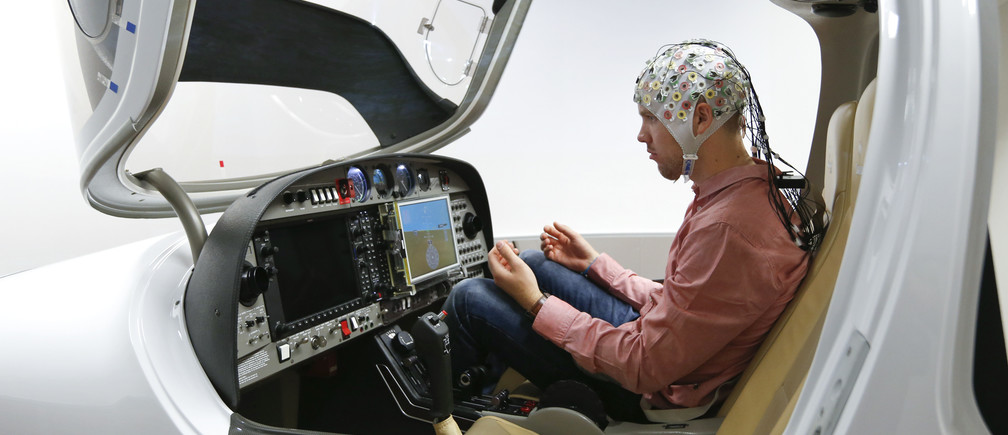 Test person Niklas Thiel sits inside a flight simulator with an electroencephalography (EEG) cap measuring brain activity, at the Technische Universitaet Muenchen (TUM) in Garching near Munich September 9, 2014.