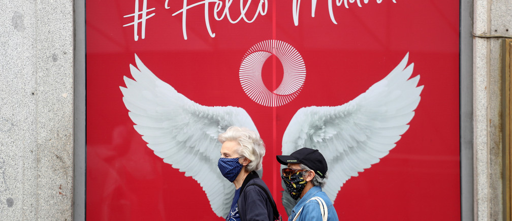 People wearing protective face masks walk past a banner amid the coronavirus disease (COVID-19) outbreak, in Madrid, Spain May 26, 2020. REUTERS/Sergio Perez - RC2BWG9R3VDN
