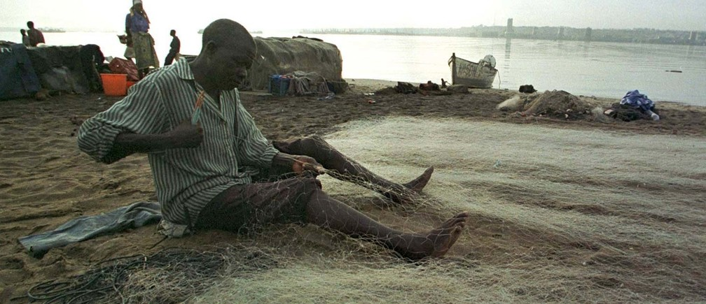 An elderly fisherman mends his nets in the early morning hours on a beach in a Luanda bay April 28.