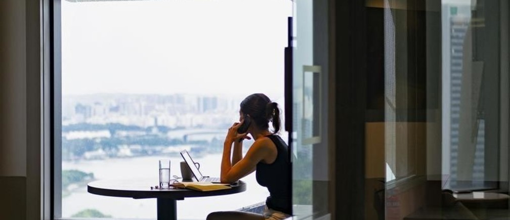 A woman answers a call while looking out the window in co-working space The Great Room's Centennial Tower location in Singapore, July 2, 2019. Picture taken July 2, 2019. REUTERS/Loriene Perera - RC122659CFA0