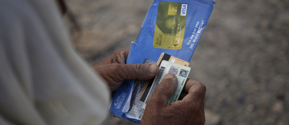 A man, fleeing a military offensive in South Waziristan, holds his national identity card and an ATM cash card while waiting to get food handouts at a distribution point for internally displaced persons (IDPs) in Dera Ismail Khan,  in Pakistan's restive North West Frontier Province, October 27, 2009. Pakistan forces killed 19 militants in an intense clash in South Waziristan on Monday while insurgents aiming to divert the army's attention launched a raid in another northwestern region, officials said. REUTERS/Faisal Mahmood   (PAKISTAN CONFLICT) - GM1E5AR1D8001
