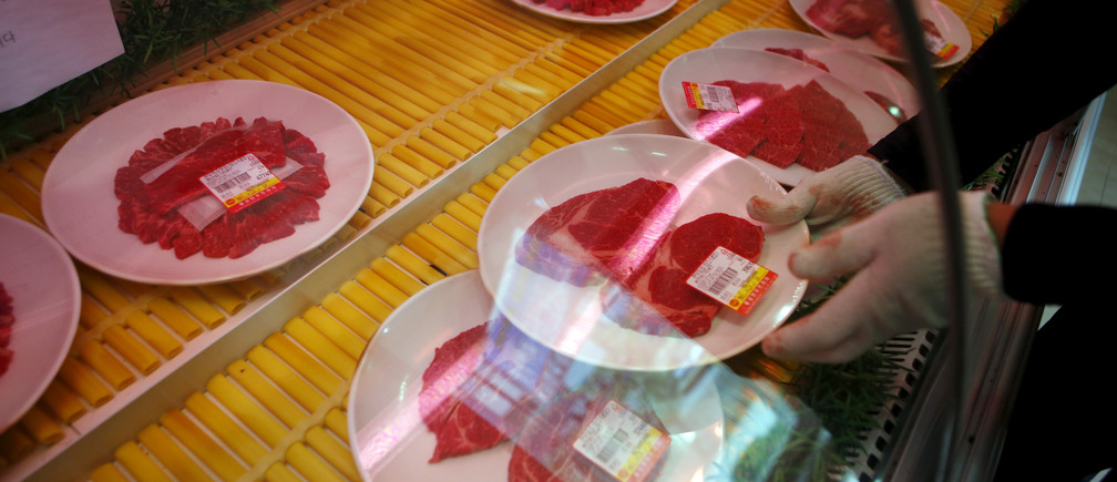 A man displays cuts of beef at a BBQ restaurant in Hongseong, South Korea, September 16, 2015.