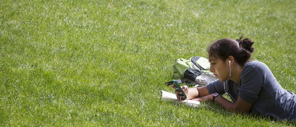 A woman lies in the grass reading a book and listening to music at Columbia University in New York, April 14, 2014. REUTERS/Carlo Allegri (UNITED STATES - Tags: SOCIETY ENVIRONMENT EDUCATION) - GM1EA4F0G6V01