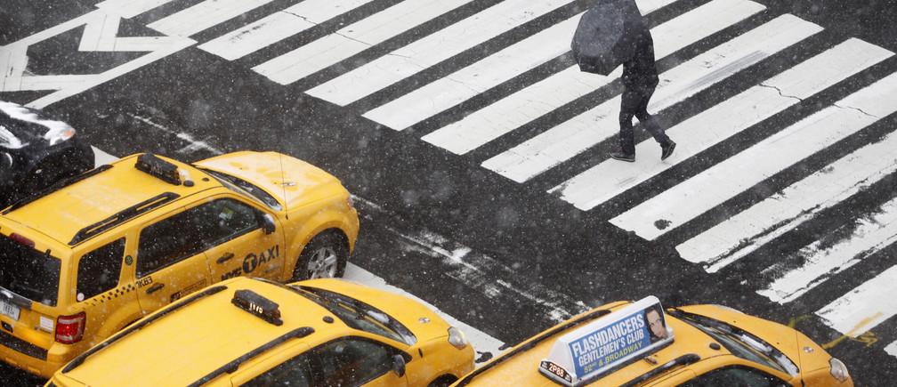 A pedestrian crosses the street during a snowstorm in New York, October 29, 2011. A rare October snowstorm bore down on the heavily populated U.S. Northeast on Saturday, with some areas bracing for up to a foot (30 cm) of snow and major power outages.   REUTERS/Jessica Rinaldi (UNITED STATES - Tags: ENVIRONMENT SOCIETY) - GM1E7AU097O01
