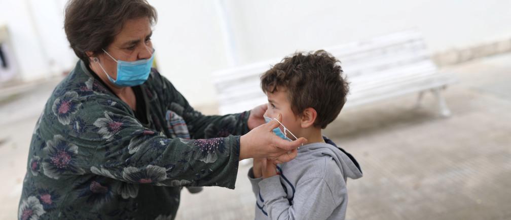 Amparo Aguilera se pone una mascarilla protectora en su nieto Kilian, de 6 años, después de que se levantaran parcialmente las restricciones para los niños, durante el brote de la enfermedad coronavirus (COVID-19), en Igualada, España, el 26 de abril de 2020.