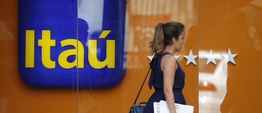 A woman walks past an Itau branch office in Rio de Janeiro January 29, 2014. Brazilian bank Itau Unibanco Holding SA said it would acquire control of leading Chilean bank CorpBanca SA, a deal worth an estimated $3.7 billion that would help it expand beyond its stagnant home turf into more dynamic markets. REUTERS/Sergio Moraes (BRAZIL - Tags: BUSINESS) - GM1EA1U05J601