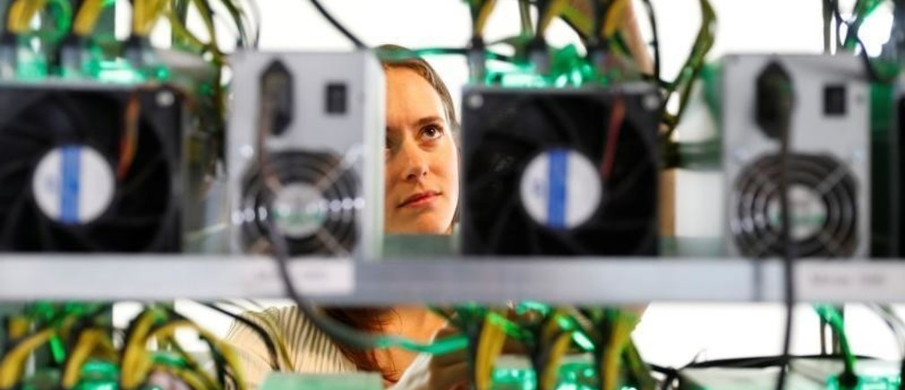 HydroMiner CEO Nadine Damblon checks cables on a miner at their cryptocurrency farming operation near Waidhofen an der Ybbs, Austria April 25, 2018.