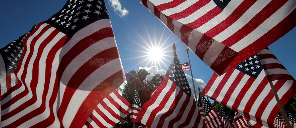 A man takes part in planting some of the 3,000 U.S. flags placed in memory of the lives lost in the September 11, 2001 attacks, at a park in Winnetka, Illinois, September 10, 2016. REUTERS/Jim Young     TPX IMAGES OF THE DAY      - S1BEUAOPVWAA