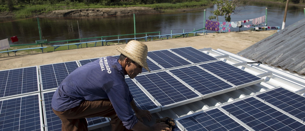 Francisco da Silva Vale, 61, cleans solar panels which power ice machines at Vila Nova do Amana community in the Sustainable Development Reserve, in Amazonas state,  Brazil, September 22, 2015. Three solar-powered machines, are producing about ninety kilos of ice per day, in a region with poor access to electric energy, which used to be produced only with diesel oil, in the Amazon rain forest. The Gelo Solar (Solar Ice) project, developed by the Mamiraua Institute for Sustainable Development and the Sao Paulo University (USP), aims to improve the life quality of the residents of the communities allowing them to preserve their fish and fruits productions which are their main economic resources. The Mamiraua Institute is also using solar energy to supply the community's homes with water and light up a soccer field. Picture taken September 22. REUTERS/Bruno Kelly - GF10000234575