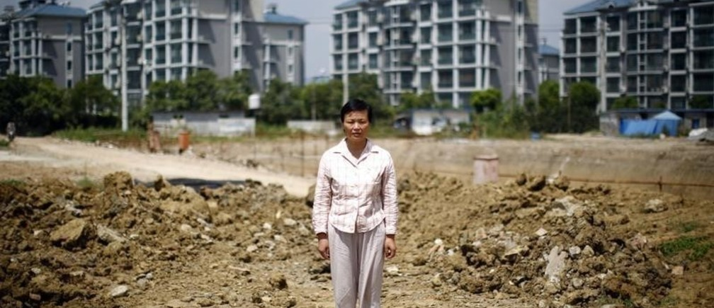 Xu Haifeng poses at a construction site area where her house stood in Wuxi, Jiangsu province, August 20, 2013. When Xu's home was razed three years ago, she went to China's capital Beijing to complain about the city and county governments that ordered the demolition. Since then she says family members have been kidnapped at least 18 times, typically having black bags thrust over their heads before being taken to a hotel-turned-illegal jail in the eastern city of Wuxi and locked for weeks in a tiny, windowless room. Xu's story is shocking even in a country that has become used to tales of arbitrary and sometimes violent land expropriations. It illustrates how the stresses from the deep indebtedness of China's local governments extend beyond banks into the lives of ordinary Chinese, as hard-up authorities resort to any means they can in a desperate scramble for funds. Picture taken August 20, 2013. REUTERS/Carlos Barria  (CHINA - Tags: BUSINESS CONSTRUCTION POLITICS LAW) - GM1E9930ESR01