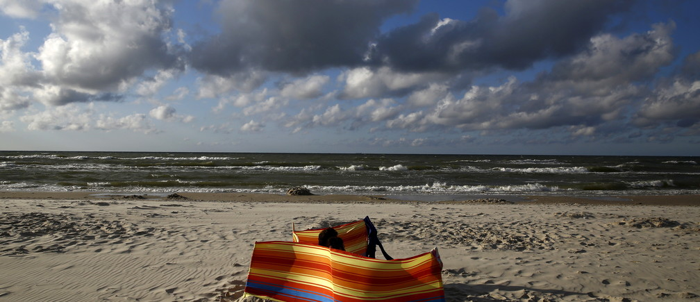 A couple sunbath on the beach in Ostrowo, northern Poland, July 20, 2015. Picture taken July 20, 2015. REUTERS/Kacper Pempel - GF10000165960
