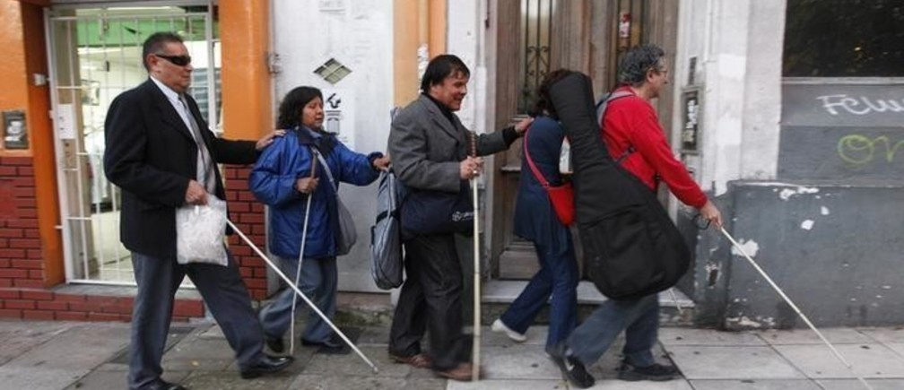 Leonardo Duarte (C), who lost his eyesight as a young adult victim of an attempted robbery, and his wife Eusebia Casimiro (2nd L), who was left blind during surgery to remove a brain tumour, walk with other visually impaired friends in Buenos Aires, May 6, 2013. Leonardo and Eusebia are two of around 400,000 blind people in Argentina, who despite having their lives improved through the legalization of guide dogs in more public places, still face a lack of jobs, a major problem according to the Association for Aid to the Blind. Picture taken May 6, 2013.       REUTERS/Enrique Marcarian