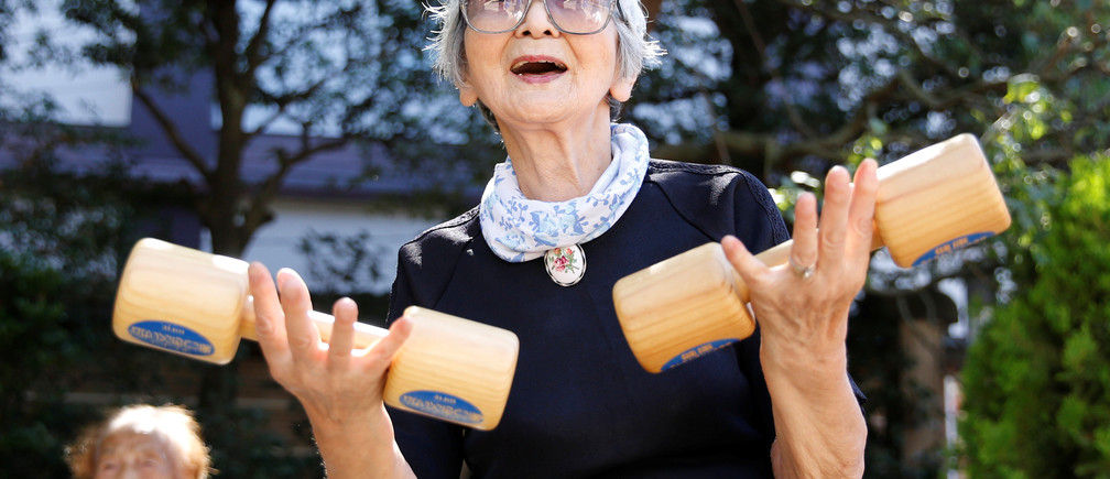 "Elderly and middle-aged people exercise with wooden dumbbells during a health promotion event to mark Japan's ""Respect for the Aged Day"" at a temple in Tokyo's Sugamo district, an area popular among the Japanese elderly, Japan, September 18, 2017.   REUTERS/Toru Hanai - RC1C0651C800"