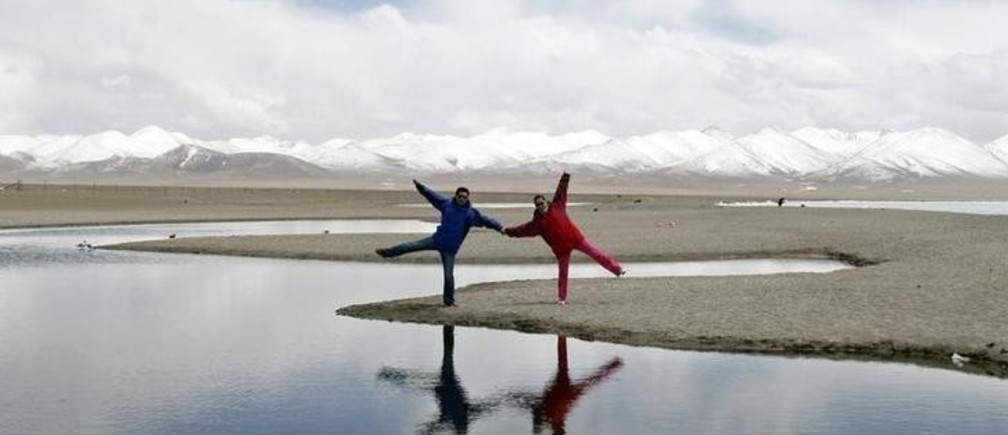 Local tourists poses for a photograph on the shores of Lake Namtso, Tibet Autonomous Region May 10, 2011. Namtso Lake, which means sacred or heaven lake in Tibetan, is 4,718 metres (15,479 feet) above sea level and is the second largest salt-water lake in China next to Qinghai Lake. Picture taken May 10, 2011. REUTERS/Rooney Chen (CHINA - Tags: SOCIETY TRAVEL)