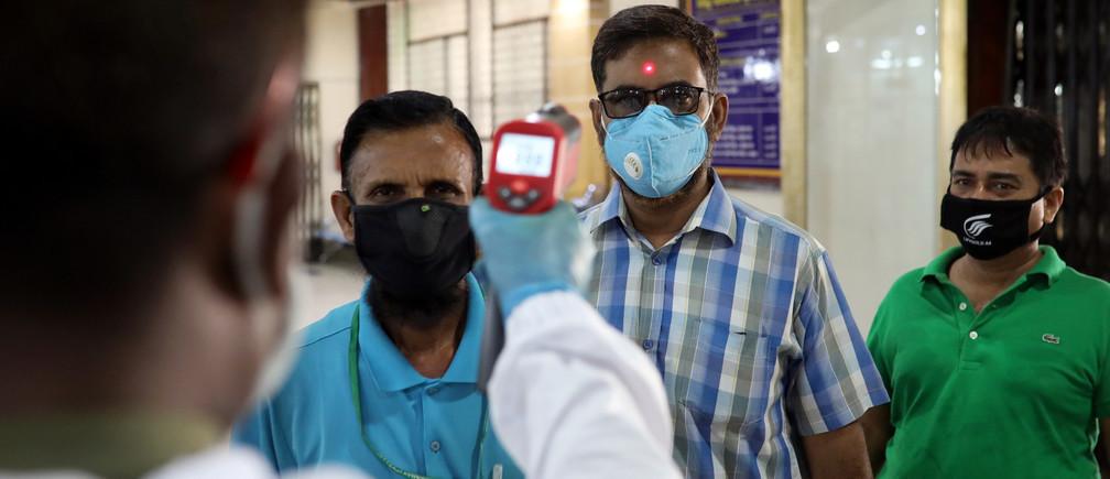 Un personal de seguridad comprueba la temperatura corporal de los clientes en Dhaka, Bangladesh, el 2 de abril de 2020.