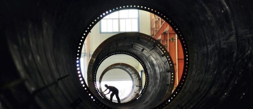 A labourer builds components of wind turbines at a wind power equipment factory in Zouping, Shandong province May 18, 2011. With profitable wind and hydropower businesses included, overall power generation losses narrowed to 6 billion yuan, Xue Jing, director of the statistics and information department under the China Electricity Council, said on the sidelines of a conference in Beijing on Tuesday. Picture taken May 18, 2011. REUTERS/China Daily (CHINA - Tags: ENVIRONMENT ENERGY BUSINESS IMAGES OF THE DAY) CHINA OUT. NO COMMERCIAL OR EDITORIAL SALES IN CHINA - RTR2MLSD