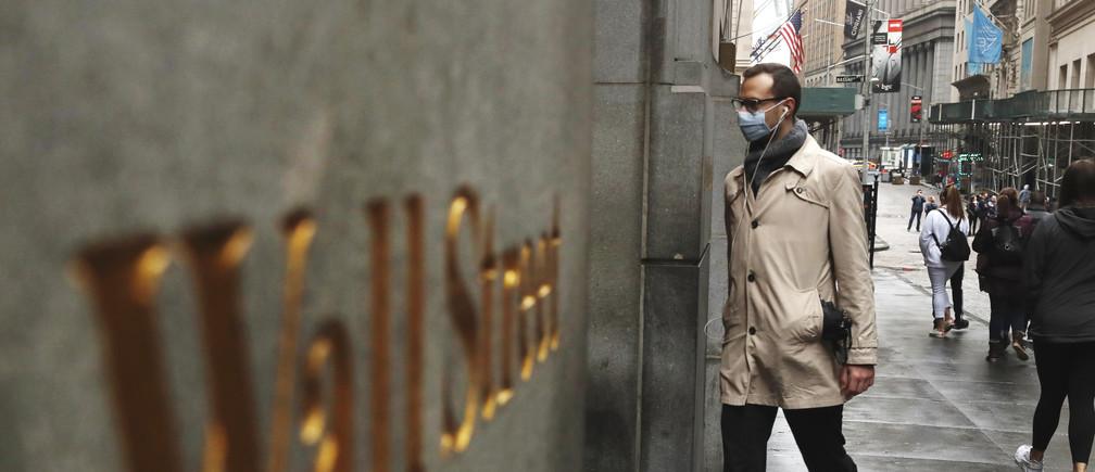 Un homme porte un masque de protection alors qu'il marche sur Wall Street lors de l'épidémie de coronavirus à New York, New York, États-Unis, le 13 mars 2020.