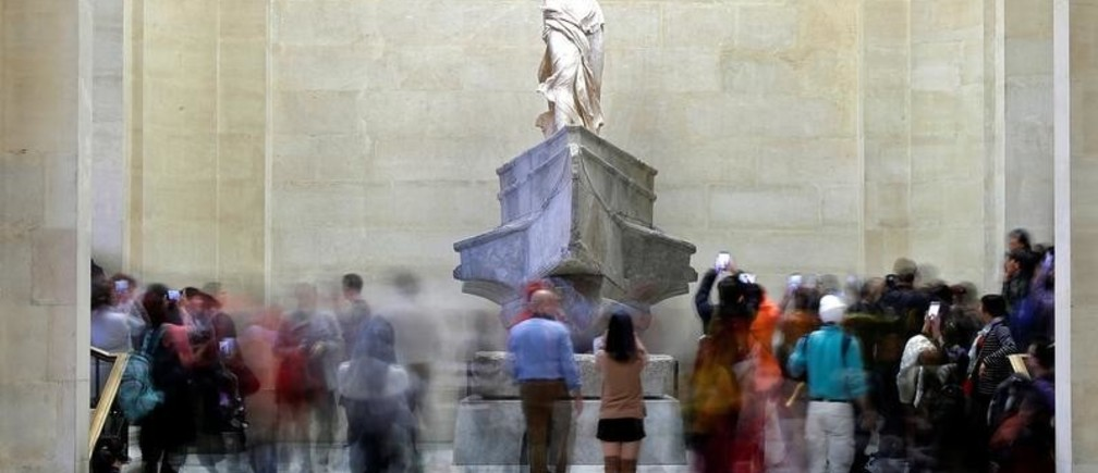 Visitors look at the Winged Victory of Samothrace, also called the Nike of Samothrace, a marble Hellenistic sculpture at the Louvre Museum in Paris, France, December 3, 2018. Picture taken December 3, 2018.  REUTERS/Charles Platiau - RC17EA5E2600