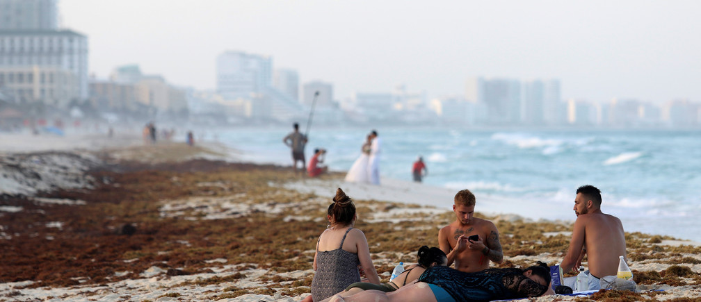 Tourists are seen on a beach covered wth seaweed in Cancun, Mexico June 24, 2019. REUTERS/Jorge Delgado - RC1913BE9290