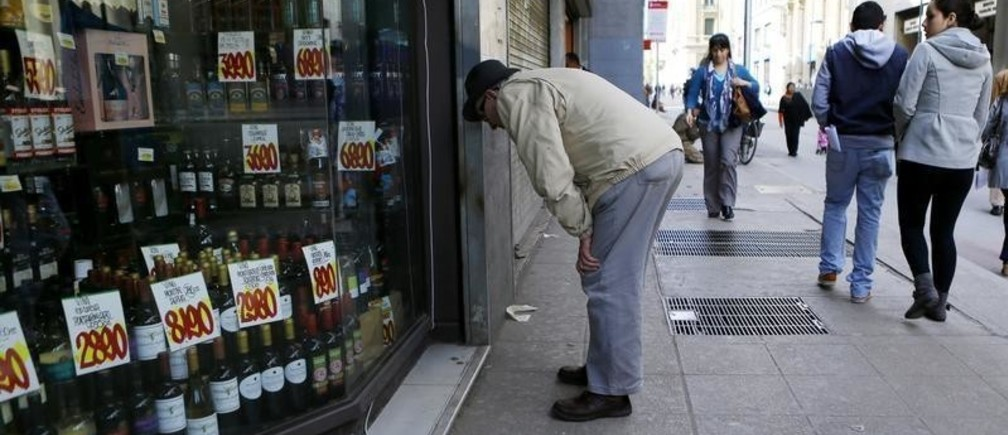 A consumer looks at a shop window along a street in downtown Santiago, August 26, 2014. REUTERS/Ivan Alvarado (CHILE - Tags: SOCIETY BUSINESS) - GM1EA8R07DR01