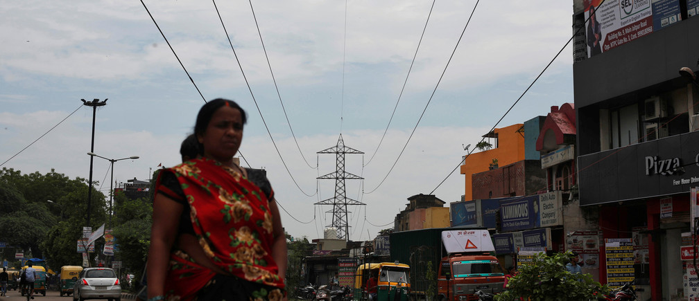 A woman walks under high-tension power lines near a coal-fired power plant in New Delhi, India, July 20, 2017. Picture taken July 20, 2017.  REUTERS/Adnan Abidi - RC1A50A31DC0