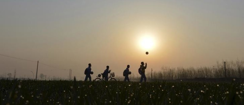 Students play with their soccer balls as they walk among crop fields to the Sunji Township Centre Primary School during sunrise in Sunji township of Shanghe county, Shandong province March 25, 2015. The rural primary school founded its male and female soccer teams in 2012 by selecting 30 players out of about 300 students. Despite the lack of infrastructures and coaching conditions, both teams have won good scores at municipal-level student soccer competitions in last two years, local media reported. China's footballing stars of the future need to start being trained from birth, the government said at the end of February as President Xi Jinping signed off on a new plan to boost the country's much-maligned efforts at the sport. Picture taken March 25, 2015. REUTERS/Stringer CHINA OUT. NO COMMERCIAL OR EDITORIAL SALES IN CHINA. TPX IMAGES OF THE DAY.