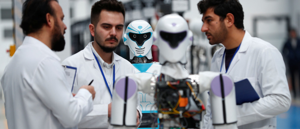 "Ozgur Akin, Chairman and founder of Akinsoft, and engineers check an ""ADA GH5"" humanoid hybrid robot at Akinrobotics, the country's first-ever factory to mass produce humanoid robots, in Konya, Turkey, December 8, 2017"