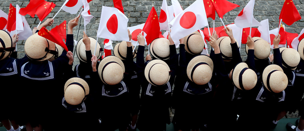 Kindergarten pupils wave national flags as Chinese Premier Li Keqiang reviews the guard of honour with Japan's Prime Minister Shinzo Abe during a welcoming ceremony before their bilateral talks at Akasaka Palace state guest house in Tokyo, Japan May 9, 2018.  REUTERS/Toru Hanai     TPX IMAGES OF THE DAY - RC18FF33DE90