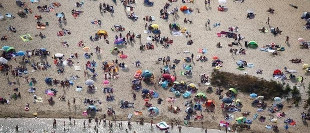 An aerial view shows people at a beach on the shores of lake Silbersee (Silver Lake) during a long-lasting heatwave over central Europe in Haltern, Germany, August 4, 2018.  REUTERS/Wolfgang Rattay