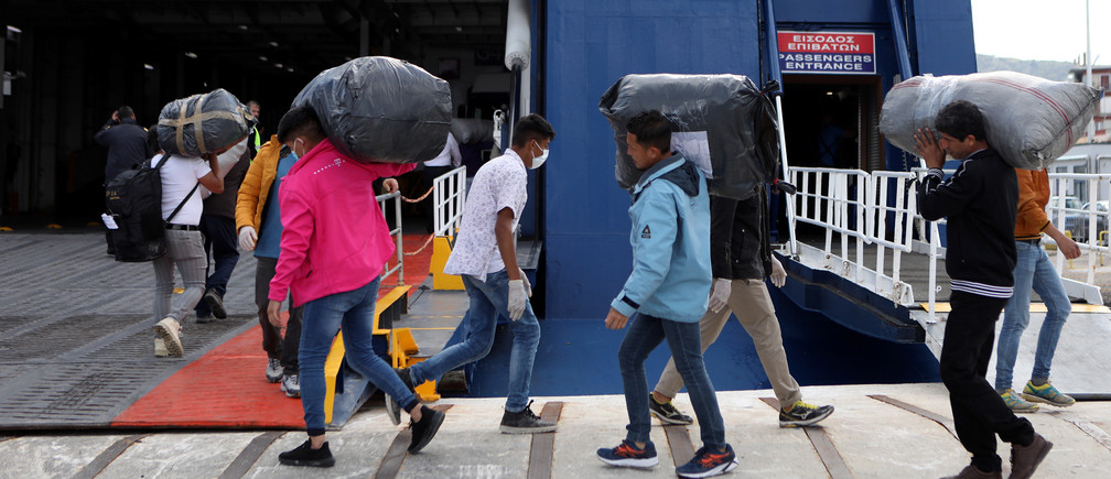 Migrants from the Moria camp carry their belongings as they board a ferry that will transfer them to the mainland as a precaution against the spread of the coronavirus disease (COVID-19) outbreak, on the island of Lesbos, Greece, May 3, 2020. REUTERS/Elias Marcou - RC24HG9YMPIW