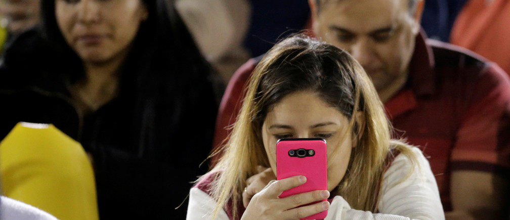 A football fan looks at a mobile phone before a match at the Defensores del Chaco stadium in Asuncion, Paraguay July 4, 2017. Picture taken July 4, 2017.   REUTERS/Jorge Adorno - RC1826ACAAB0