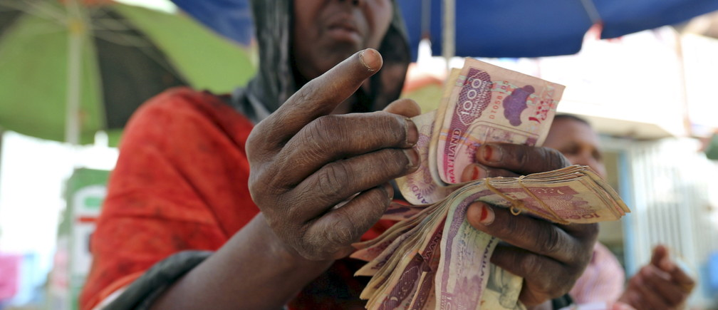A money changer counts local currency notes at a local bureau where $100 US dollar exchanges for 750,000 Somaliland shillings in Hargeysa May 19, 2015 REUTERS/Feisal Omar - RTX1DNUE
