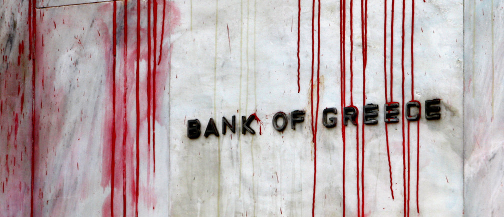 A branch of the Bank of Greece is seen stained with red paint thrown by demonstrators during a protest in central Athens, December 6, 2010.Greek police fired teargas at stone-throwing youths marching in Athens to mark the anniversary of the police killing of a 15-year-old, which triggered the country's worst riots in decades in 2008. REUTERS/Yannis Behrakis (GREECE - Tags: CIVIL UNREST)