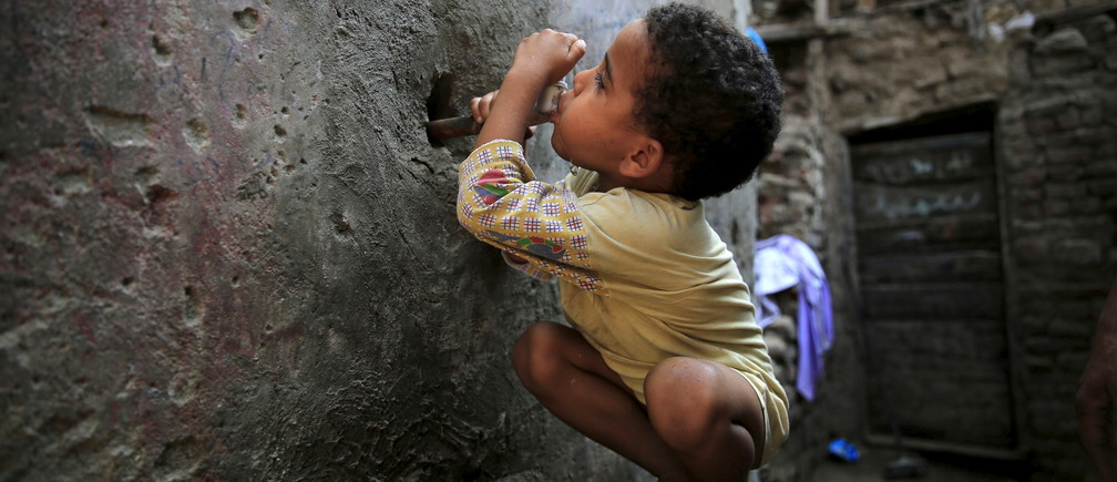An Egyptian child drinking from a water faucet in Cairo.