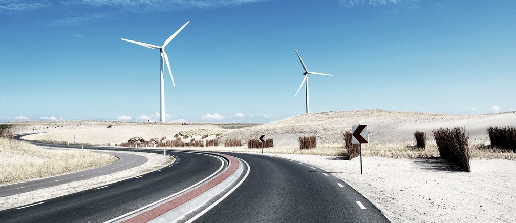 A wind farm beside a road.