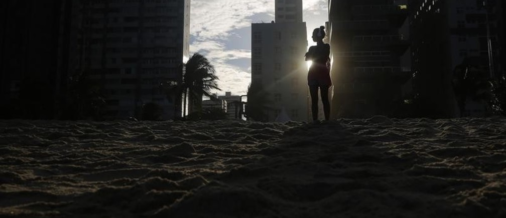 """A woman listens to music as the sun sets as seen between buildings on Boa Viagem beach in Recife June 30, 2014. In a project called """"On the Sidelines"""" Reuters photographers share pictures showing their own quirky and creative view of the 2014 World Cup in Brazil.  REUTERS/Brian Snyder    (BRAZIL - Tags: SPORT SOCCER WORLD CUP TRAVEL ENVIRONMENT SOCIETY) - GM1EA710EOX01"""