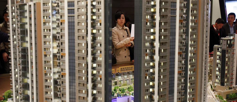 A potential buyer looks at a model of Riva, one of the latest developments by Sun Hung Kai Properties, in Hong Kong February 19, 2014. REUTERS/Bobby Yip