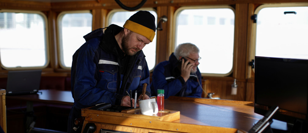 """Skipper and third generation fisherman from Thyboron Poul-Erik Rom, 35, works on the bridge with his father Ejvind Rom, 65, on their ship Anna-Lise in the village of Thyboron in Jutland, Denmark, March 18, 2019. Each year Poul Erik and his father land fish worth some 25 million Danish Crowns ($3.75 million) from their vessel, one third of which come from British waters. """"I like the unpredictability of fishing. Sometimes we catch 200 kilos, sometimes two tonnes, and we never know what prices we will get,"""" he said. """"It seems like we have to sail further and further away from the shore to find the fish,"""" said Poul Erik, who worries what will happen if he is restricted access to British water. The problem for Poul Erik and his father is that as the water warms due to climate change, the fish they rely on such as cod and haddock tend to swim towards colder waters nearer the UK and further north. REUTERS/Andrew Kelly  SEARCH """"KELLY JUTLAND"""" FOR THIS STORY. SEARCH """"WIDER IMAGE"""" FOR ALL STORIES. - RC1B99AB4630"""