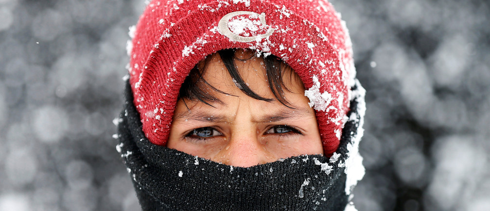 An Internally displaced Afghan boy looks on as he stands outside his shelter during a snowfall in Kabul, Afghanistan February 5, 2017. REUTERS/Mohammad Ismail      TPX IMAGES OF THE DAY - RTX2ZO5V