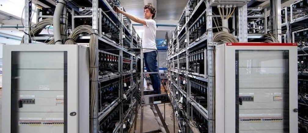 An employee works on bitcoin mining computers at Bitminer Factory in Florence, Italy, April 6, 2018. Picture taken April 6, 2018. REUTERS/Alessandro Bianchi