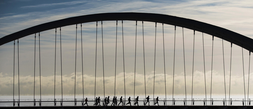 """A group of joggers run across the Humber Bay Arch Bridge during extreme cold temperatures in Toronto, February 16, 2015. Toronto experienced some of the coldest weather of the year reaching -25C (-13F) on Sunday, as Environment Canada lifted its """"extreme cold weather alert"""" Monday when temperatures warmed to -13C (8.6F), according to local reports.   REUTERS/Mark Blinch (CANADA - Tags: ENVIRONMENT TPX IMAGES OF THE DAY) - GM1EB2H060R01"""