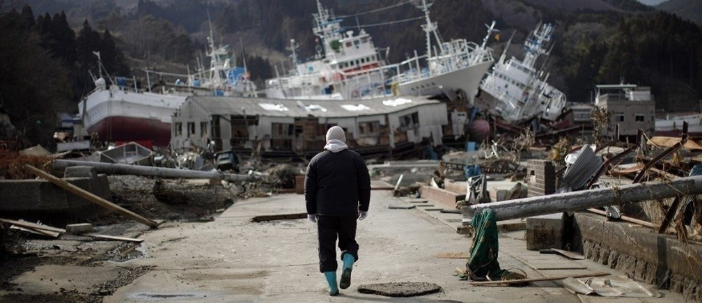 A man walks next to port area destroyed by the earthquake and tsunami in Kessenuma town, in Miyagi prefecture March 28, 2011. Japan appeared resigned on Monday to a long fight to contain the world's most dangerous atomic crisis in 25 years after high radiation levels complicated work at its crippled nuclear plant. REUTERS/Carlos Barria (JAPAN - Tags: DISASTER ENVIRONMENT)  FOR BEST QUALITY IMAGE: ALSO SEE GM1E74S05GS01. - RTR2KI4R