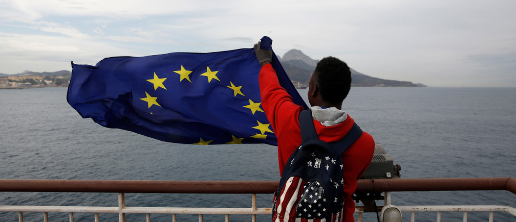 An African migrant holds a European Union flag on board a ferry to Algeciras after having awaited in CETI, the short-stay immigrant centre in Spain's north African enclave of Ceuta to be transferred to mainland Spain, February 23, 2017.